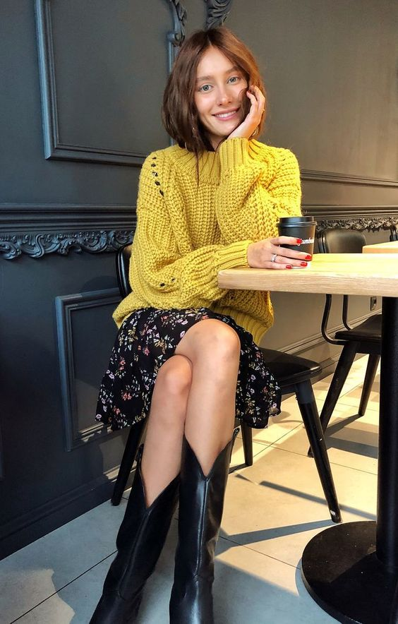 a mustard chunky sweater over a black floral dress and black cowboy boots for the fall