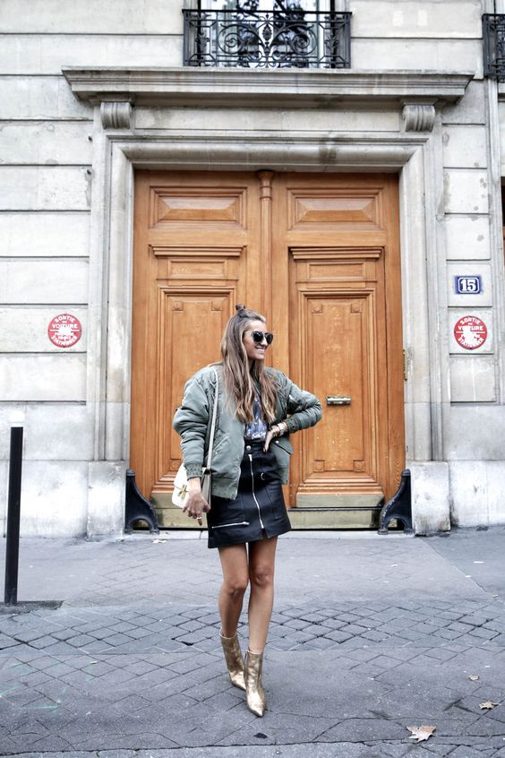 a casual fall look with a printed tee, a black zip mini skirt, an olive green bomber jacket, gold boots and a white bag