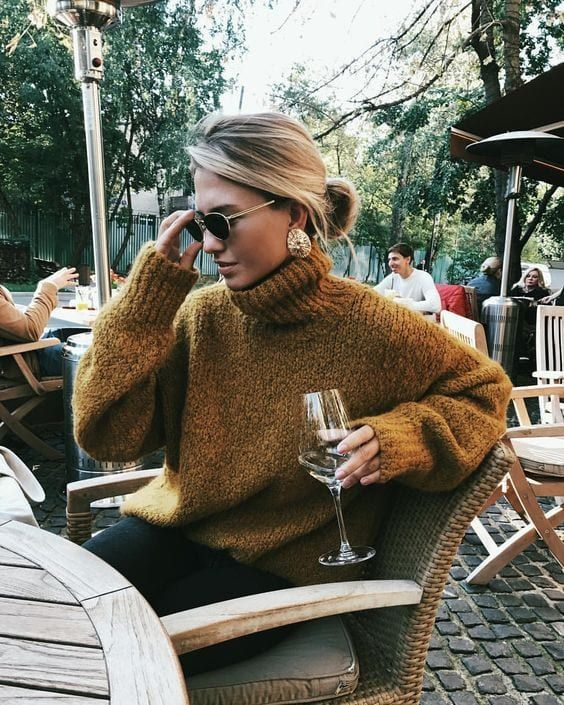 a mustard-colored oversized sweater, black jeans and statement earrings that elevate the whole outfit