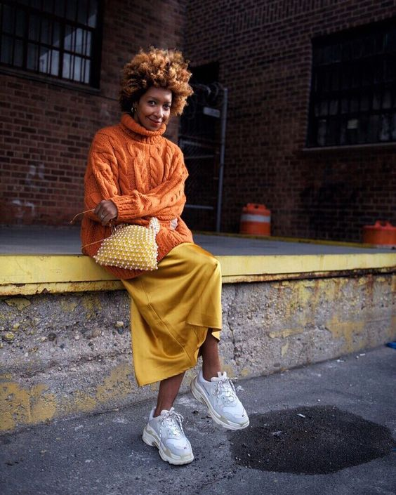 a super colorful fall outfit with an oversized orange turtleneck sweater, a gold slip skirt, white trainers and an embellished bag