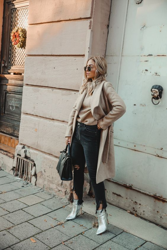 a casual chic fall look with a tan jumper, black ripped jeans, silver booties, a tan coat and a black bag
