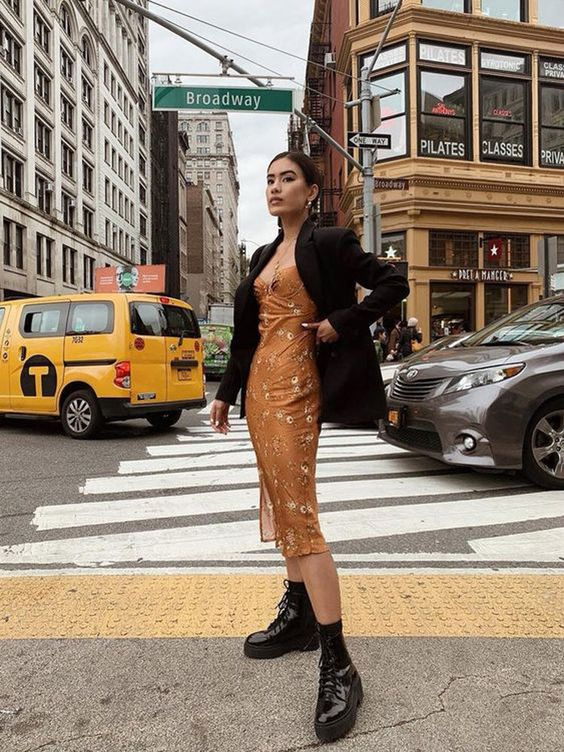 a fall look with a mustard floral midi dress, black boots, an oversized black blazer for a bold touch
