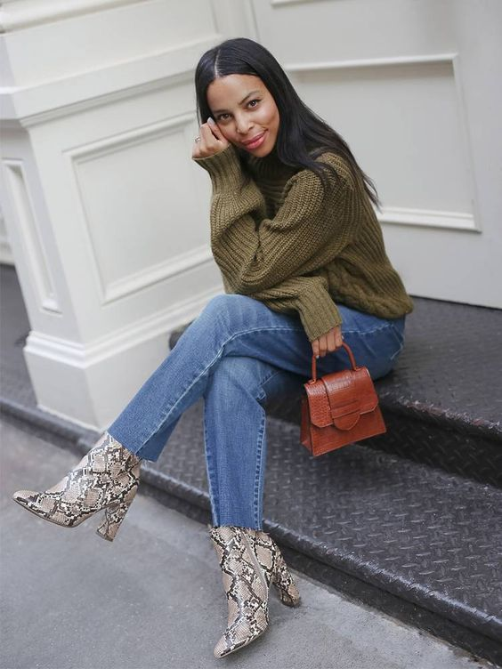 a pretty fall-colored outfit with a green chunky sweater, blue jeans, snakeskin print booties and a rust-colored mini bag