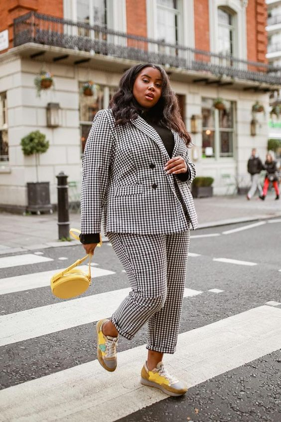 a black and white checked pantsuit, bold yellow trainers and a matching round bag and a black turtleneck