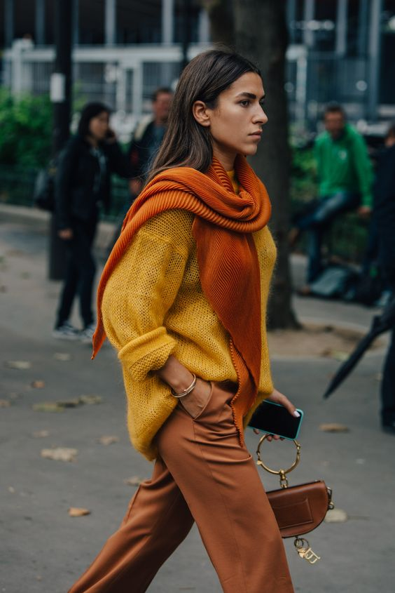 a bold fall outfit with rustc trousers, a yellow oversized sweater, an orange scarf and a brown bag with a ring handle