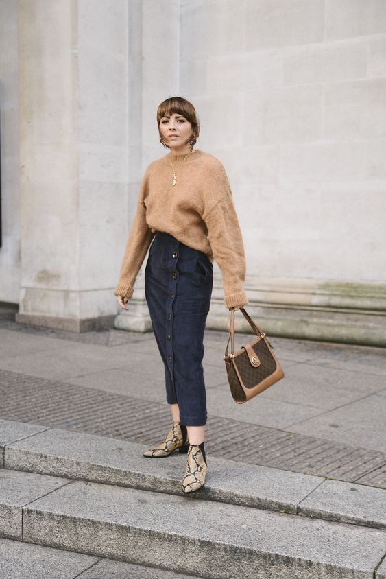 a tan oversized sweater, a navy button up denim midi, snakeskin print booties and a two tone bag