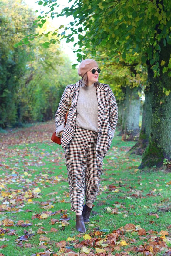 a French chic look with a bold plaid pantsuit, a grey turtleneck, burgundy booties, a tan beret, a deep red bag
