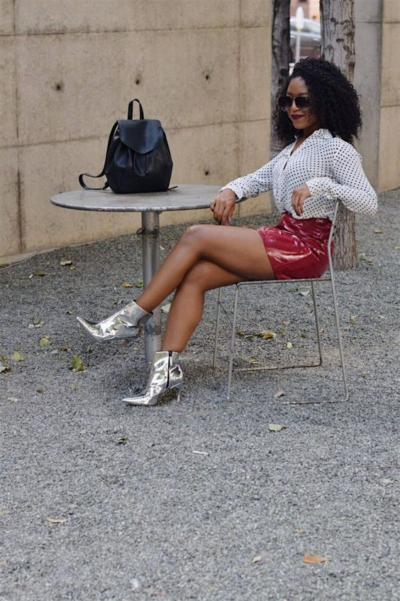 a white polka dot shirt, a red patent leather skirt, silver boots, a black backpack for a bold look