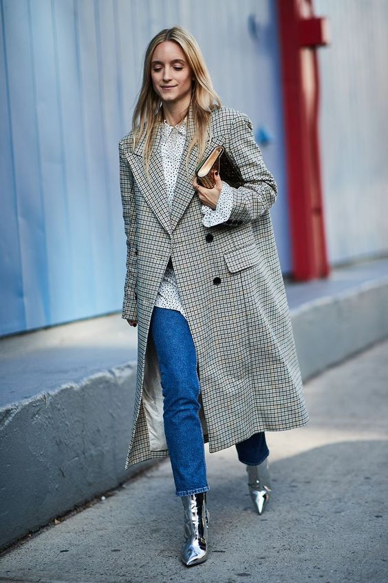 a refined look with an oversized spot shirt, blue cropped jeans, silver boots, an oversized plaid coat and a clutch
