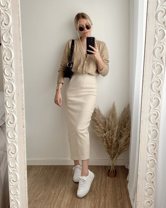 an elegant monochromatic fall outfit with a tan cardigan tucked into a creamy midi pencil skirt, white sneakers and a black bag