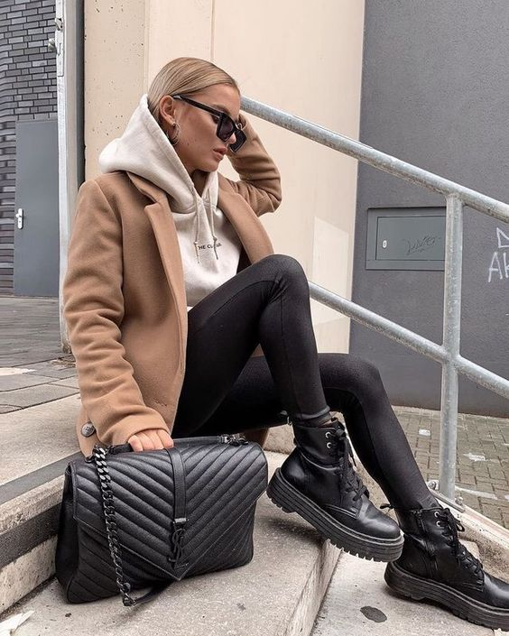a white hoodie, black leggings, combat boots, a tan cropped coat and a black black bag for a comfy look