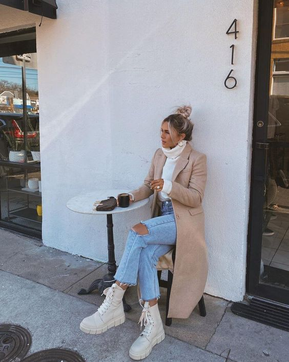 a white turtleneck sweater, blue ripped jeans, creamy combat boots, a tan coat and a small bag