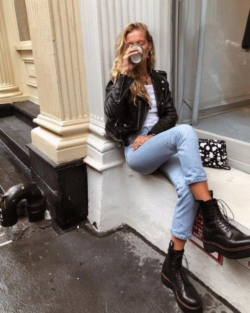 a timeless look with a white tee, blue jeans, a black leather jacket, black combat boots and a printed bag