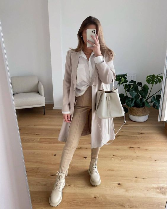 a neutral work outfit with a white shirt, tan trousers, an off-white trench, creamy combat boots and a creamy bag