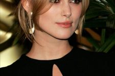 Keira Knightley wearing brunette hair with honey and blonde balayage, with long curtain bangs for a super refined and chic look