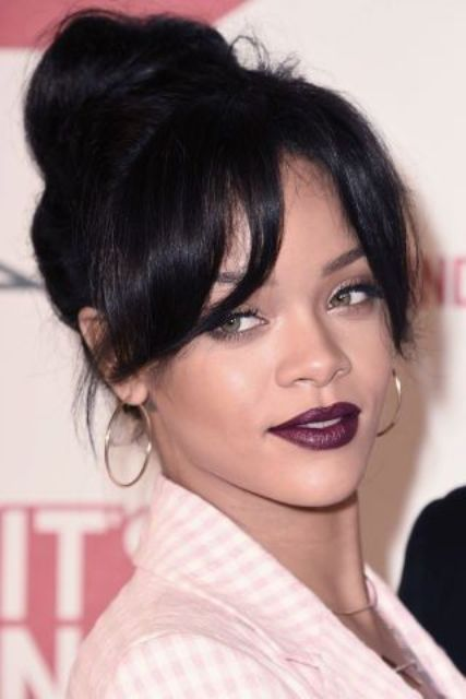 Rihanna wearing a top knot and elegant curtain bangs looks amazing, this is a chic and timeless look