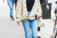 Selena Gomez wearing a black turtleneck, blue cropped flare jeans, black loafers and a creamy cardigan and a bag