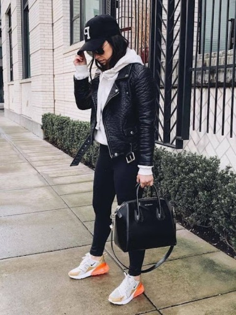 With black cap, black bag, skinny pants and white and orange sneakers