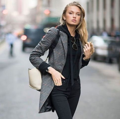 With black jeans and beige bag