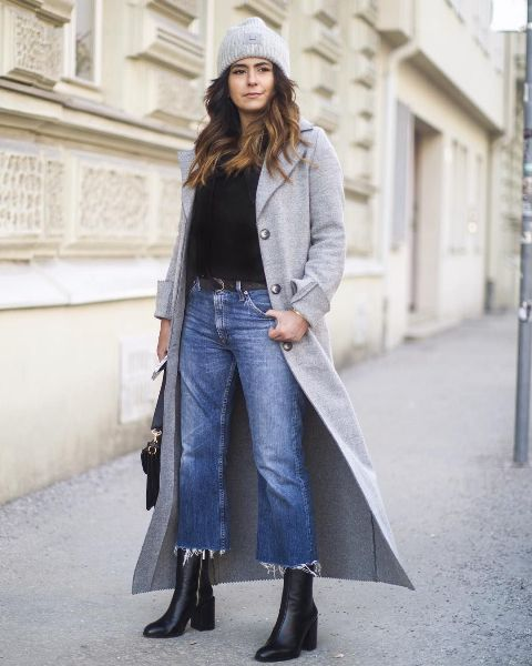 With black shirt, gray maxi coat, black mid calf boots, bag and hat