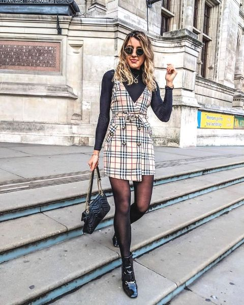 With black turtleneck, black leather bag, rounded sunglasses and black patent leather ankle boots