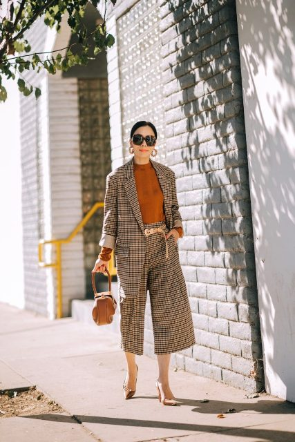 With brown sweater, brown bag, golden belt and pumps