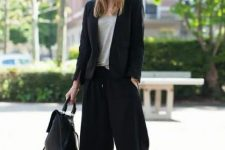 With gray loose shirt, black leather backpack and black pumps