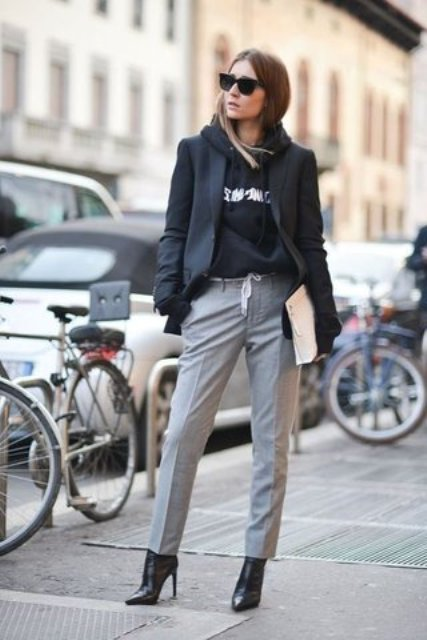With gray trousers, sunglasses, white clutch and black high heeled boots