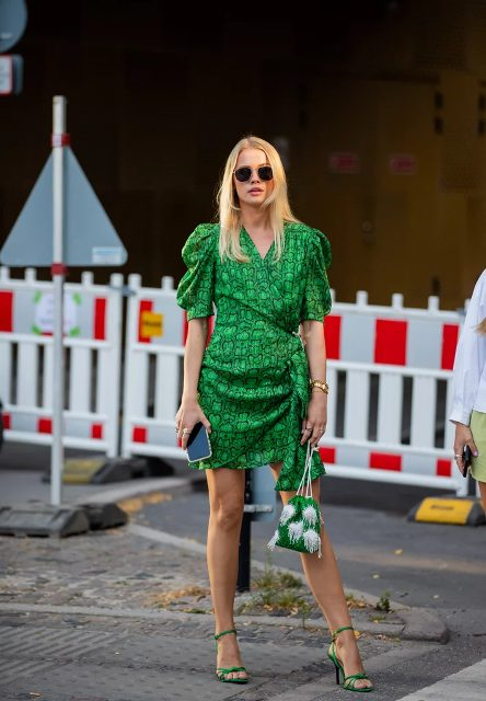 With green and white embellished bag, rounded sunglasses and green ankle strap high heels