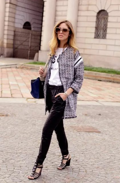 With labeled t-shirt, navy blue bag, black satin pants and embellished shoes