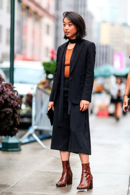 With orange shirt, black scarf, black clutch and printed leather mid calf boots