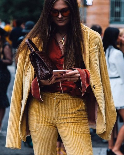 With oversized sunglasses, marsala long sleeved button down shirt and dark brown leather bag