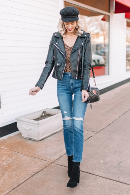 With printed V-neck shirt, black leather jacket, cap, suede boots and black leather bag