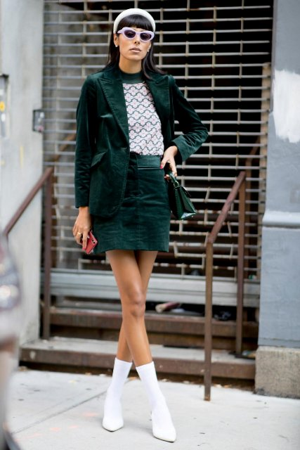 With printed shirt, green leather mini bag, white framed sunglasses, white headband and white mid calf sock boots