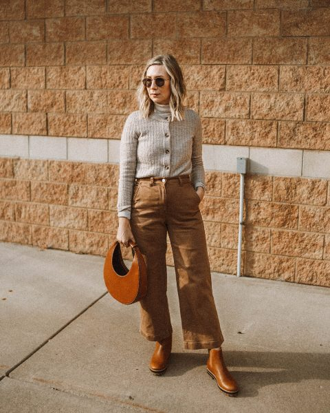 With turtleneck, gray cardigan, brown leather bag and brown flat boots
