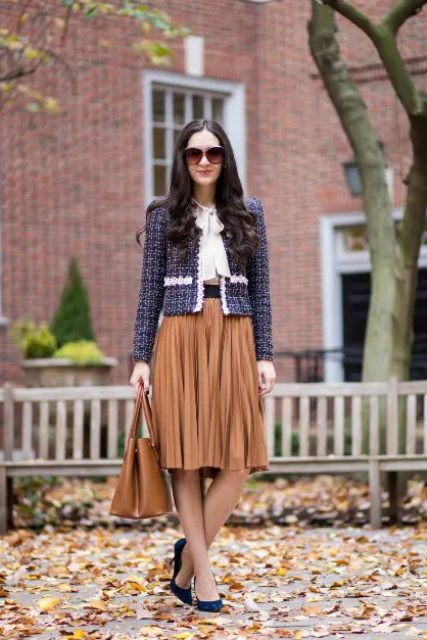 With white blouse, pleated knee-length skirt, brown bag and navy blue suede pumps