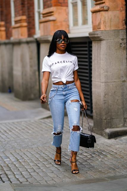 With white labeled t-shirt, black chain strap bag and high heels