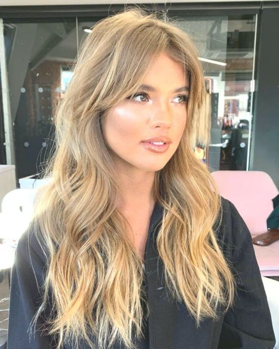 a beautiful blonde balayage with curtain bangs and long waves down is a very sexy hairstyle with a gorgeous volume