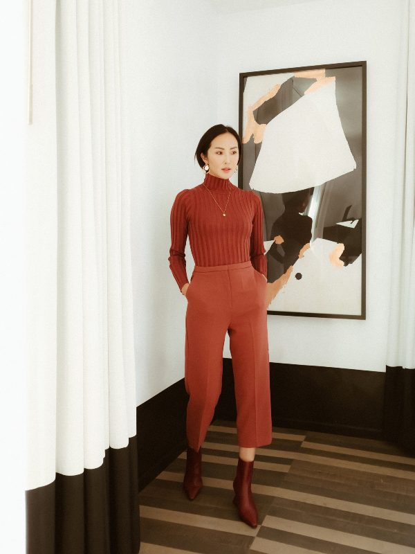 a beautiful monochromatic work look with a ribbed red turtleneck, cropped trousers, burgundy boots, a necklace and statement earrings