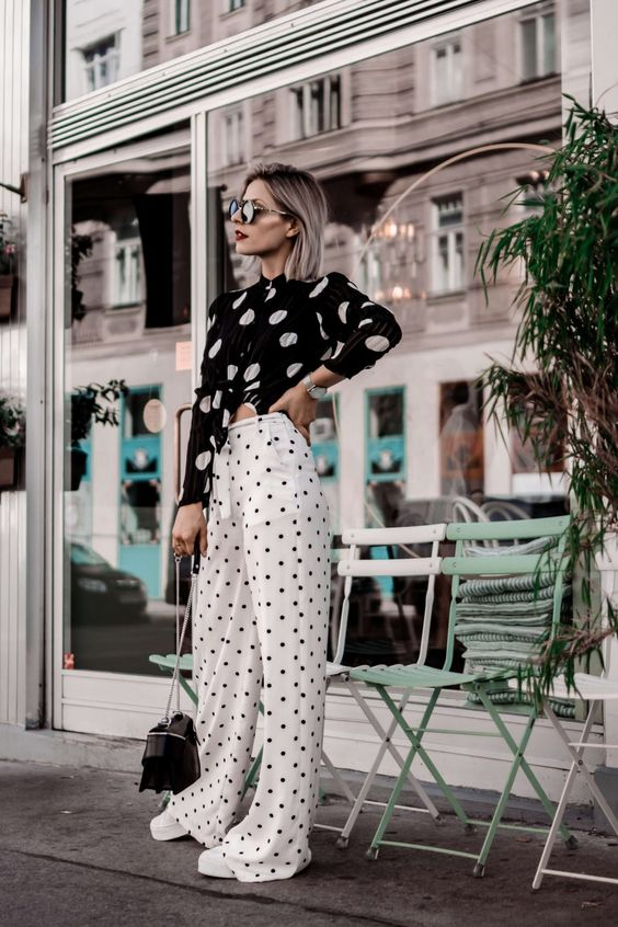 a black and white look with a cutout polka dot top and white polka dot trousers, white shoes and a black bag