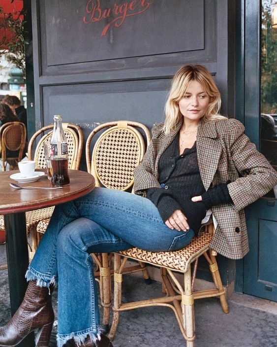 a black button up cardigan, a plaid blazer, blue flare jeans and burgundy boots for a Parisian-style look