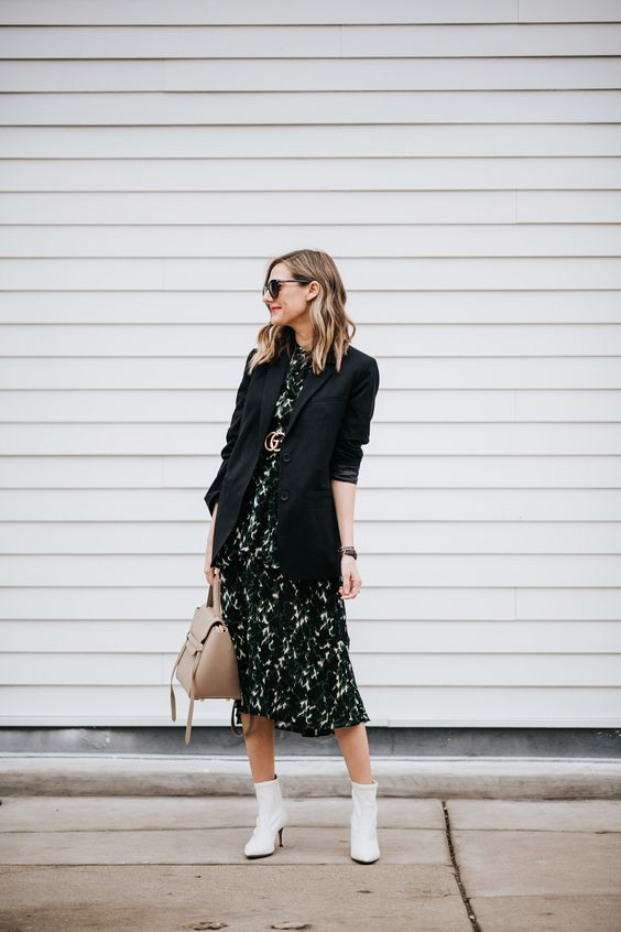 a black printed midi dress accented with a logo belt, a black oversized blazer, white booties, a tan tote for a chic work look