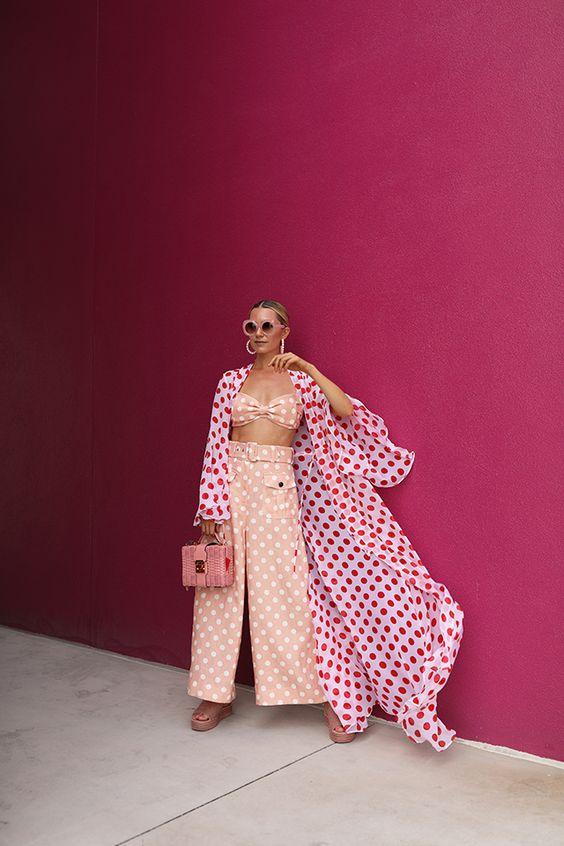 a blush polka dot set with a crop top and wide leg trousers, blush platform shoes, a pink bag and a white polka dot kimono