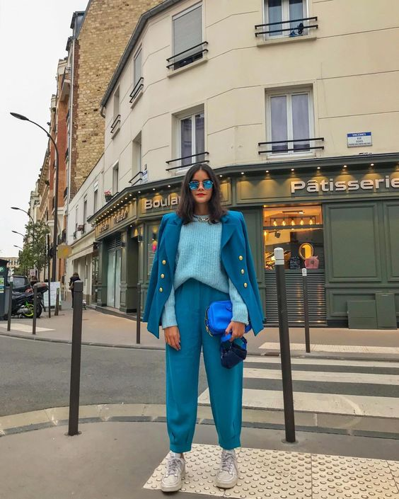 a bold blue pantsuit, a light blue jumper, white sneakers, an electric blue bag and blue sunglasses