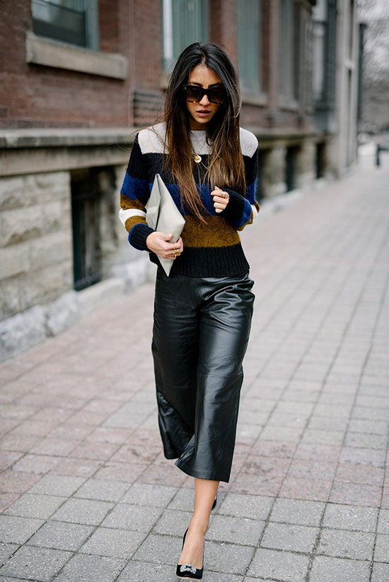 a bold outfit with a striped color block sweater, black culottes, black shoes and a neutral clutch for work