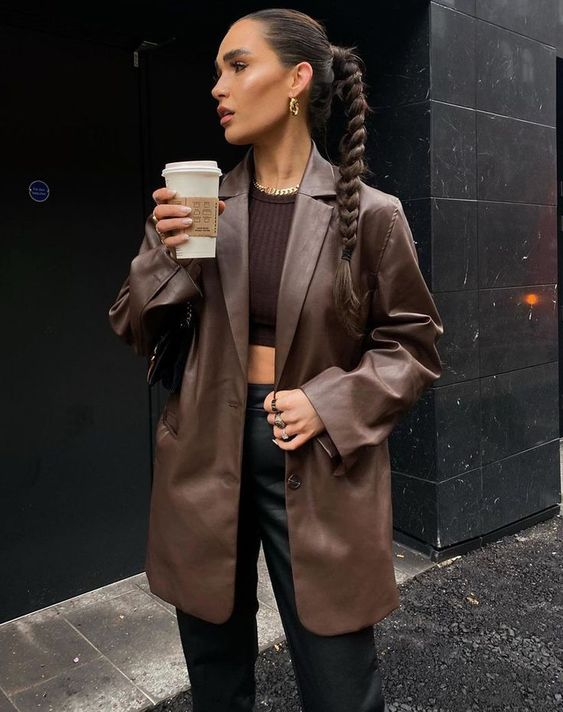 a brown crop top, a brown oversized leather blazer, black leather pants, statement jewelry for a bold look