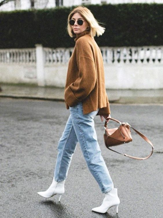 a brown oversized sweater, blue jeans, white booties and a brown bag compose a simple fall look