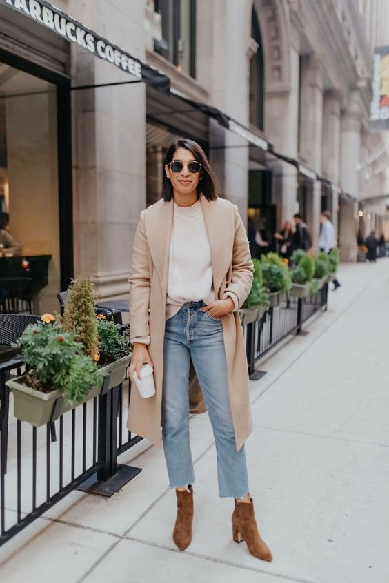 a casual fall look with a white jumper, a tan coat, blue jeans, brown booties is great for work, too