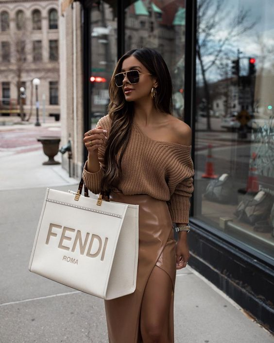 a chic beige outfit with a chunky one shoulder sweater and a tan leather wrap midi skirt, statement earrings and sunglasses