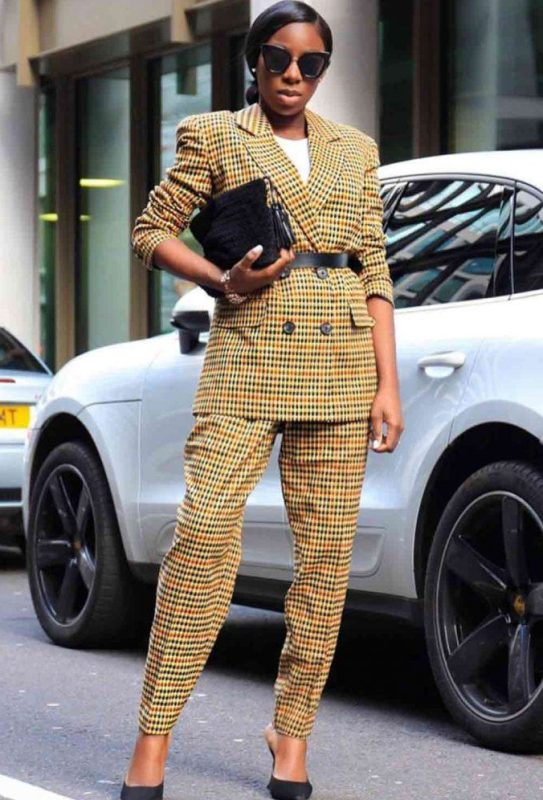 a chic yellow printed pantsuit with an oversized blazer, a black belt, black heels and a bag for a bold look